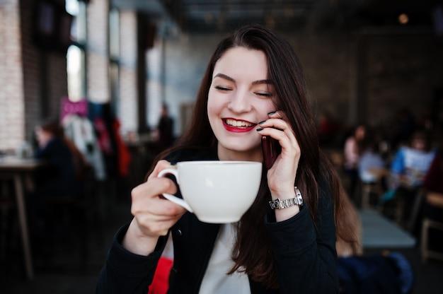 Menina morena sentada no café com uma xícara de cappuccino e falando do telefone móvel.
