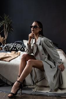 Menina morena sexy vestindo casaco e lingerie na cama