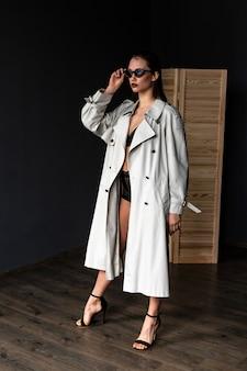 Menina morena sexy vestindo lingerie e casaco