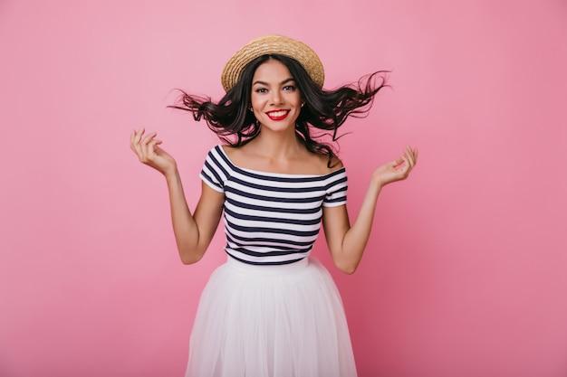 Menina morena sonhadora com pele bronzeada brincando com cabelos ondulados. mulher latina despreocupada em saia exuberante e chapéu de palha sorrindo.
