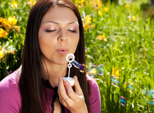 Menina morena soprando bolha de sabão contra uma grama de fundo