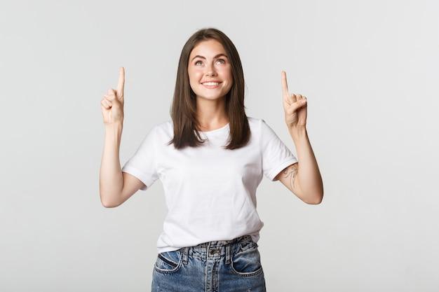 Menina morena sorridente atraente apontando os dedos para cima, mostrando o logotipo.