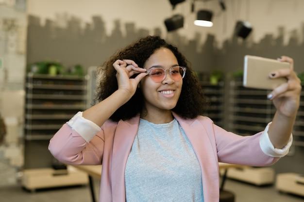 Menina morena sorridente com smartphone fazendo selfie na loja de ótica enquanto experimenta um novo modelo de óculos