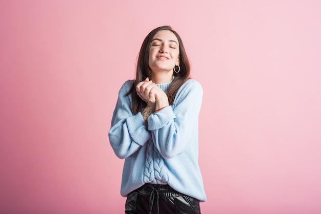 Menina morena sorridente e feliz em estúdio em fundo rosa