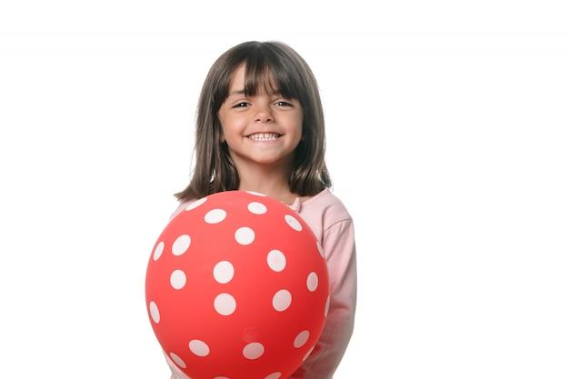 Menina morena sorrindo para a câmera com um balão no fundo branco