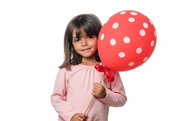 Menina morena sorrindo para a câmera com um balão