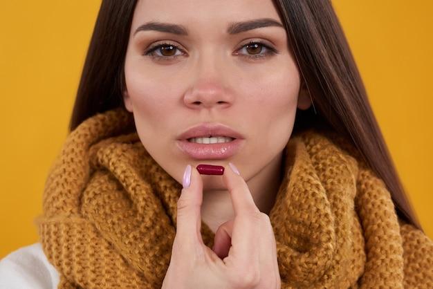 Menina morena tem poses frias com comprimidos em fundo amarelo