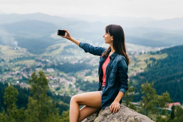 Menina morena tomando selfie com smartphone alto nas montanhas.