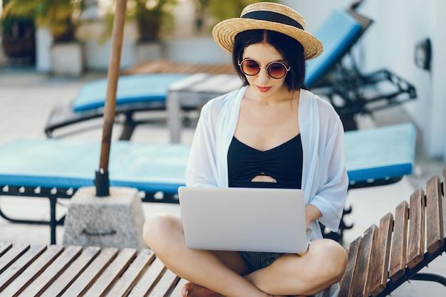 Menina morena trabalhando em seu computador à beira da piscina