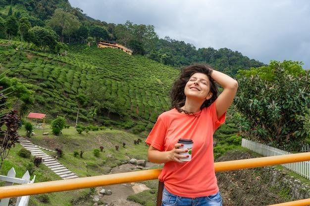 Menina morena turista gosta de chá de uma xícara de artesanato no contexto de um vale de chá verde.