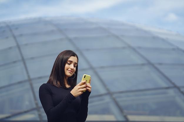Menina morena usando seu celular enquanto ela está explorando uma nova cidade