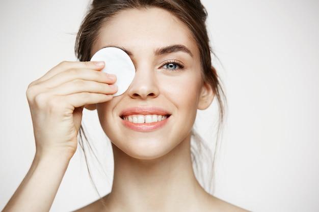Menina moreno bonita com o olho escondido da pele perfeita limpa atrás da esponja do algodão que sorri olhando a câmera sobre o fundo branco. cosmetologia e spa.