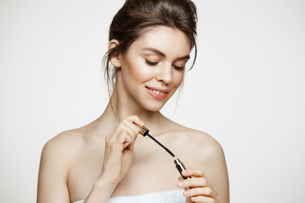 Menina moreno bonita com pele limpa perfeita que sorri guardando o rímel sobre o fundo branco. tratamento facial.