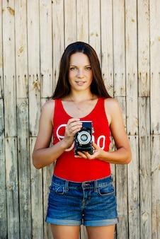 Menina moreno bonita nova no short vermelho da camisa e das calças de brim que levanta com uma câmera no fundo de madeira rústico.