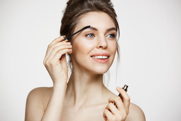 Menina moreno bonita nova que sorri olhando as sobrancelhas da pintura da câmera com rímel sobre o fundo branco. spa de beleza e cosmetologia.