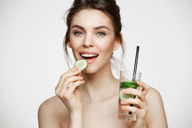 Menina moreno nova positiva que sorri olhando a câmera que come a fatia do pepino que guarda o vidro da água sobre o fundo branco. beleza e saúde.