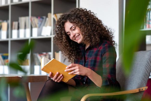 Menina moreno que senta-se na cadeira e que sorri felizmente durante um livro de leitura na biblioteca.