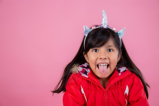 Menina mostrando a língua vestida como unicórnio