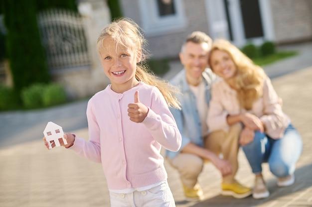 Menina mostrando a placa da casa e os pais atrás