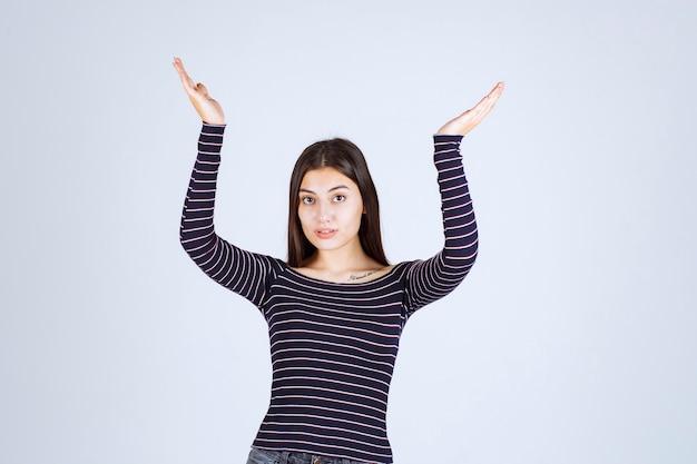 Menina mostrando a quantidade ou medidas de um produto.