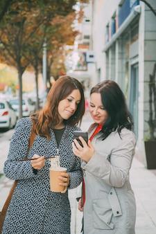 Menina mostrando a sua amiga um e-mail enquanto ela come macarrão chinês