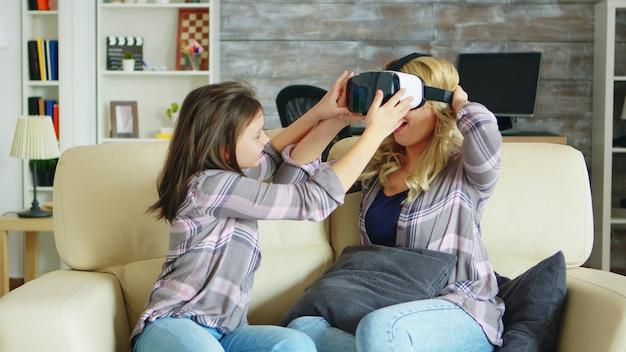 Menina mostrando a sua linda mãe como você usa fone de ouvido de realidade virtual. mãe e filha se divertindo.