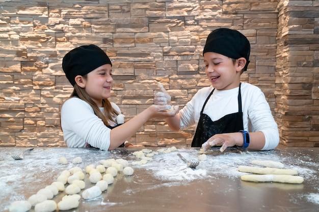 Menina mostrando ao irmão a massa que ela está preparando e ele a aprova com um polegar para cima