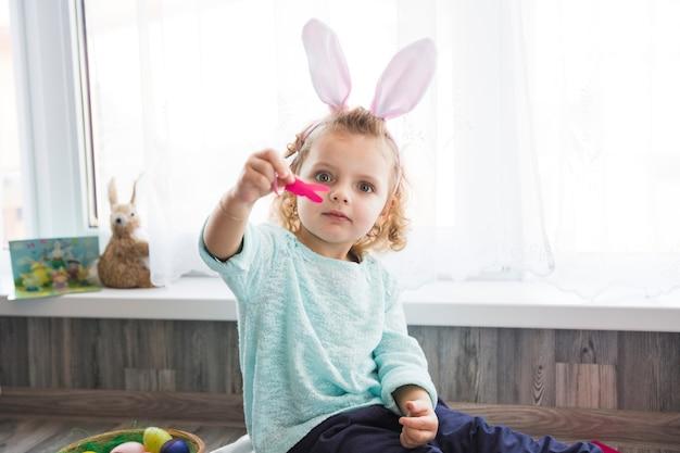 Menina mostrando coelho de papel