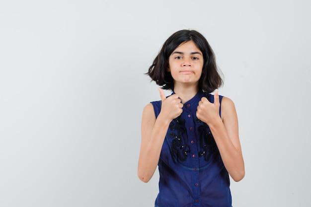 Menina mostrando dois polegares para cima, lábios curvos na blusa azul