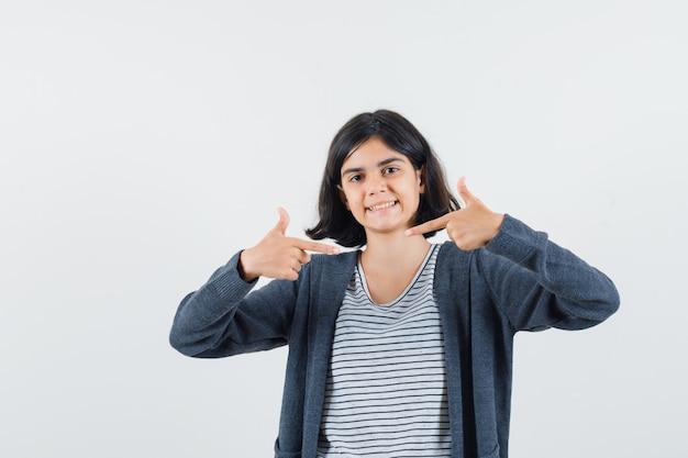 Menina mostrando gesto de arma em camiseta, jaqueta e parecendo alegre