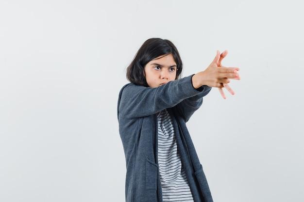Menina mostrando gesto de arma em camiseta, jaqueta e parecendo confiante