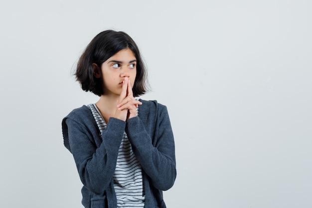Menina mostrando gesto de arma em camiseta