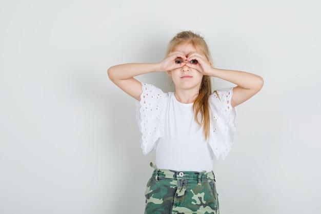 Menina mostrando gesto de óculos em camiseta branca