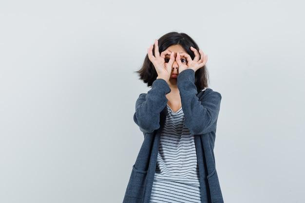 Menina mostrando gesto de óculos em uma camiseta