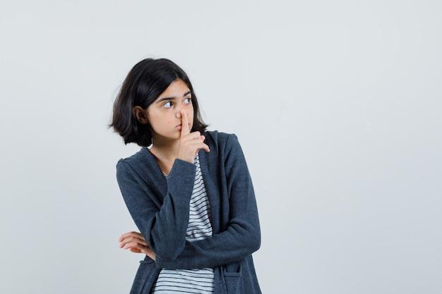 Menina mostrando gesto de silêncio em camiseta, jaqueta e parecendo preocupada