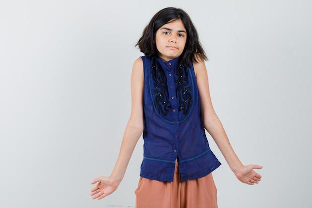 Menina mostrando gesto impotente encolhendo os ombros com blusa azul e saia