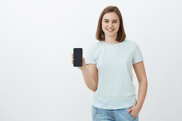 Menina mostrando o novo telefone que os pais compraram para o novo período escolar. encantada e satisfeita jovem encantadora mostrando a tela do smartphone e falando sobre um aplicativo legal que encontrou na loja online sobre uma parede cinza
