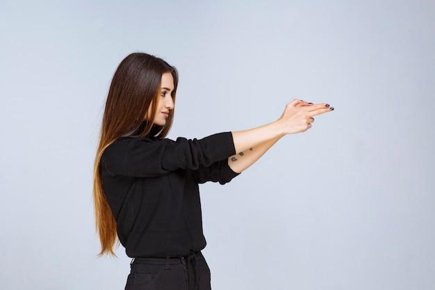 Menina mostrando sinal de arma na mão. foto de alta qualidade