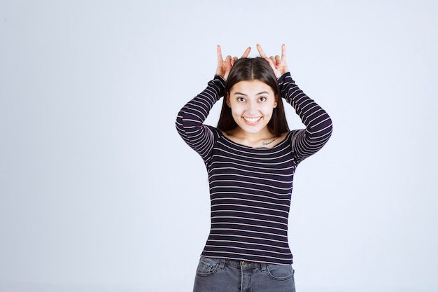Menina mostrando sinal de orelha de coelho ou lobo.