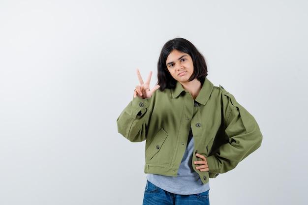 Menina mostrando sinal de vitória no casaco, camiseta, jeans e com sorte, vista frontal.