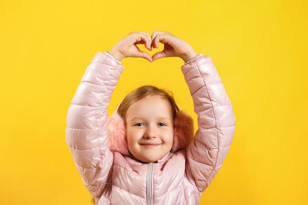 Menina, mostrando um coração com os dedos na cabeça.
