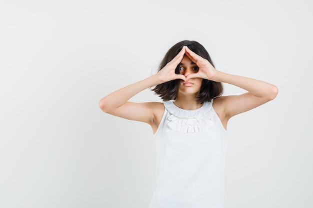 Menina mostrando um gesto de coração na blusa branca, vista frontal.
