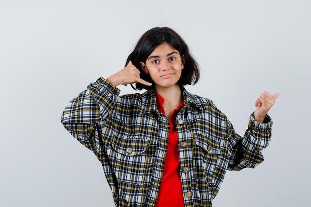 Menina mostrando um gesto de telefonema enquanto aponta para trás na camisa, vista frontal da jaqueta.