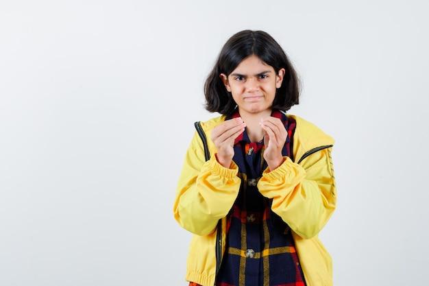 Menina mostrando um gesto delicioso em camisa xadrez, jaqueta e parecendo confiante. vista frontal.