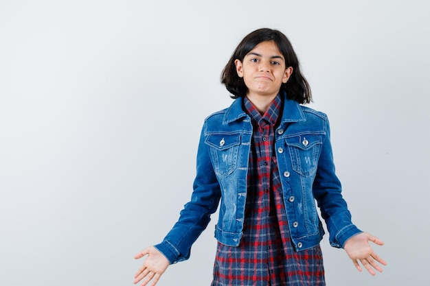 Menina mostrando um gesto impotente na camisa, jaqueta e olhando perplexa, vista frontal.