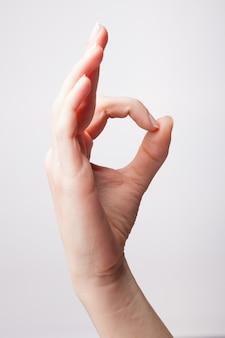 Menina mostrando um sinal de ok com a mão