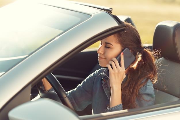 Menina motorista com telefone celular