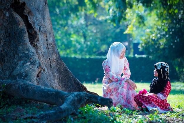 Menina muçulmana asiática com uma família que vive e relaxa debaixo de uma árvore nas férias. na casa deles, pela manhã, o sol brilha lindamente.