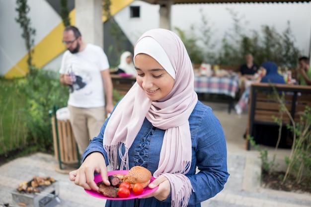 Menina muçulmana com hijab comendo comida de churrasco