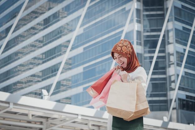 Menina muçulmana com sacola de compras